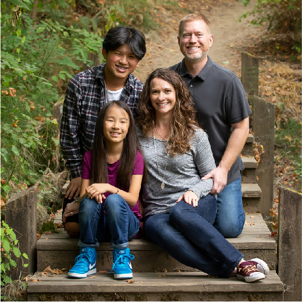 young family portrait of four on wooden stairs at Stella Olson park sherwood