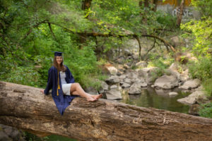 Portrait of Senior girl cap and gown on downed log over river George Rogers Park woods Willamette Lake Oswego