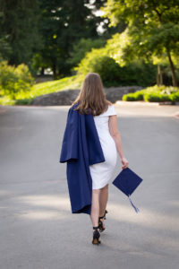 Portrait of senior girl walking away in cap and gown George Rogers Park Willamette Lake Oswego