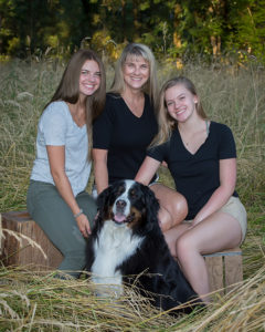 Portrait of Kim Elliott with daughters and Bernese Mountain dog in field grass West Linn