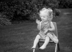 black and white photo of little girl sitting in chair clapping hands in park Canby