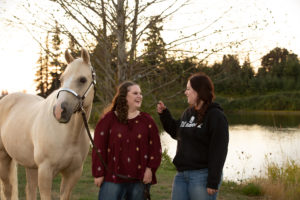 Portrait of senior girls laughing with horse on lake Canby