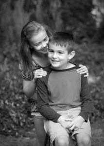 black and white portrait of big sister whispering to little brother oregon city