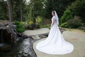 Portrait of beautiful bride by water feature and woods