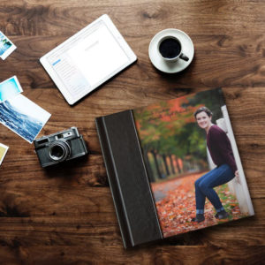 Photo album on table with coffee and camera