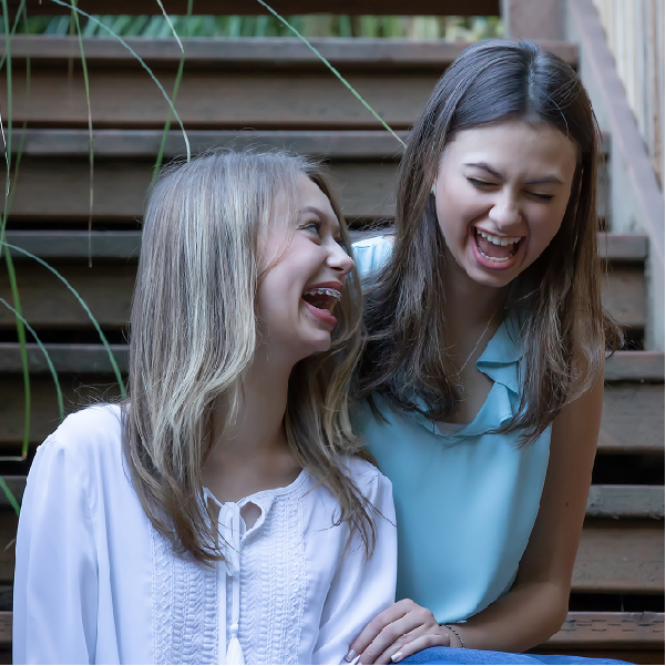 Portrait of Sisters laughing sitting on stairs West Linn